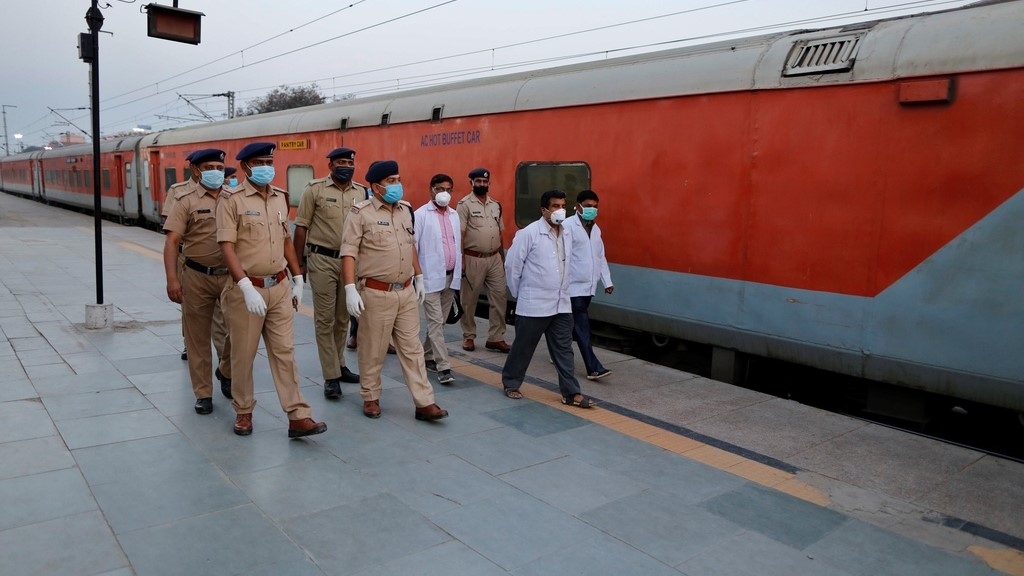 Railway officials walk through a deserted railway station platform in Prayagraj, India, Tuesday, March 24, 2020. Indian Prime Minister Narendra Modi Tuesday announced a total lockdown of the country of 1.3 billion people to contain the new coronavirus outbreak. For most people, the new coronavirus causes only mild or moderate symptoms. For some it can cause more severe illness. (AP Photo/Rajesh Kumar Singh)
