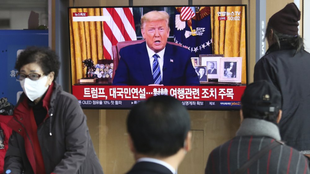 "People watch a TV screen showing a live broadcast of US President Donald Trump's speech at the Seoul Railway Station in Seoul, South Korea, Thursday, March 12, 2020. Trump announced he is cutting off travel from Europe to the U.S. and moving to ease the economic cost of a viral pandemic that is roiling global financial markets and disrupting the daily lives of Americans. The Korean letters read: ""Trump national speech."" (AP Photo/Ahn Young-joon)"