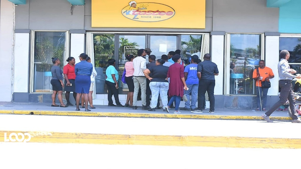 Tastee customers form a line outside the popular patty restaurant on Tuesday. (Photos: Marlon Reid)