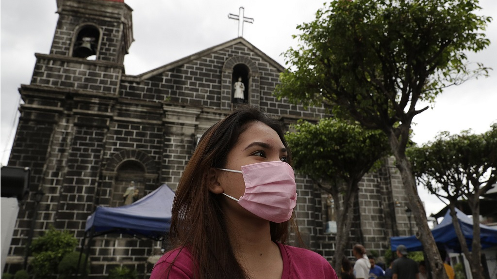 A woman wearing a protective mask walks outside a church in Mandaluyong, east of Manila, Philippines on Sunday, Feb. 2, 2020.  (AP Photo/Aaron Favila)