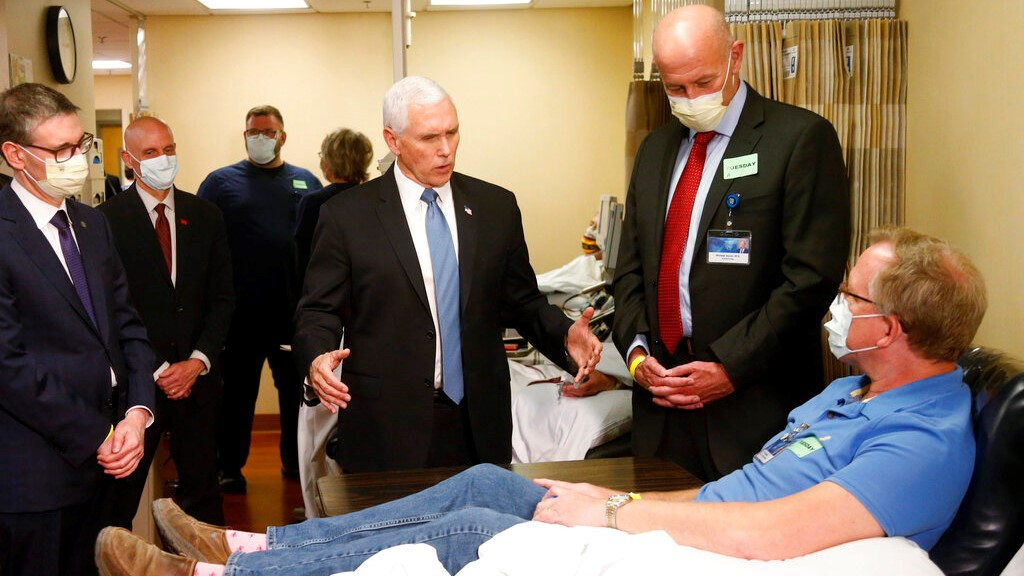Vice President Mike Pence, center, visits Dennis Nelson, a patient who survived the coronavirus and was going to give blood, during a tour of the Mayo Clinic Tuesday, April 28, 2020, in Rochester, Minnesota (AP Photo/Jim Mone)