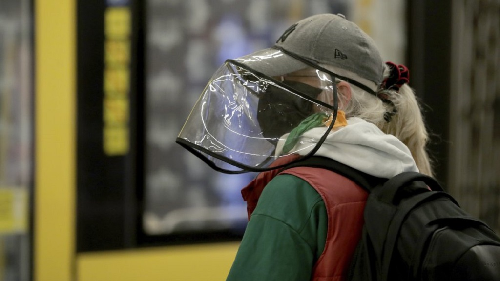 A traveler with protective gear waits for the arrival of a subway train in a station in Berlin, Germany, Monday, April 27, 2020. From today on face masks are mandatory in vehicles of the public transport in Berlin due to the coronavirus outbreak. (AP Photo/Michael Sohn)