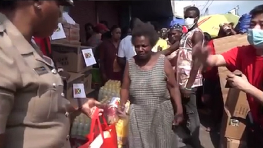 A member of the Jamaica Constabulary Force assists a Chinese wholesale operator in the handing over of gift packages to downtown Kingston residents on Thursday.