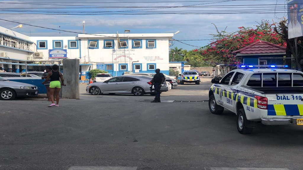 A heavily armed police officer at the gate of the Hunts Bay Police Station in St Andrew hours after a jailbreak at the facility on Sunday.
