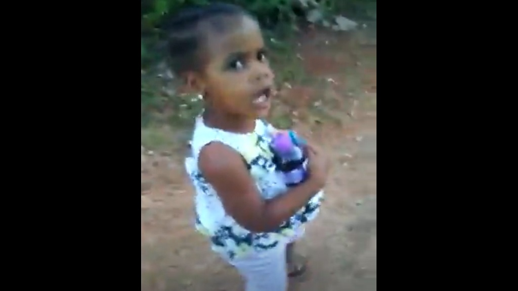 A screengrab from a video of a little child forcefully delivering the Government's message for Jamaicans to 'tan a unno yard'.