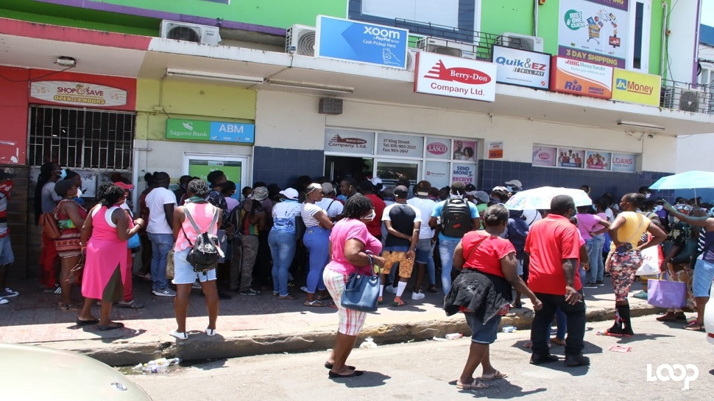 Persons crowd outside a cambio in Linstead, St Catherine on Wednesday.