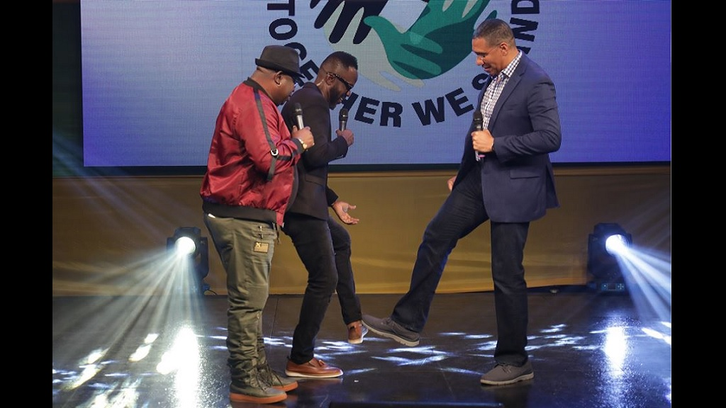 Prime Minister Andrew Holness (right), and comedian, Ian 'Ity' Ellis (centre) touch their shoes together in greeting during the 'Telethon Jamaica-Together We Stand' virtual fund-raising concert on Sunday (April 12). Looking on ​at left is comedian, Alton 'Fancy Cat' Hardware. (Photo: OPM)