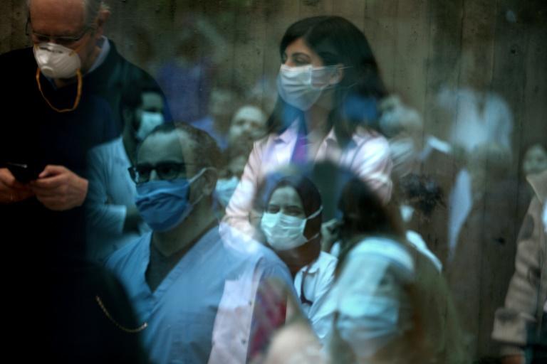 L'équipe de soignants de l'hôpital Saint-George à Beyrouth écoute un groupe de musique qui se produit pour eux, à travers une paroi vitrée, le 24 avril 2020