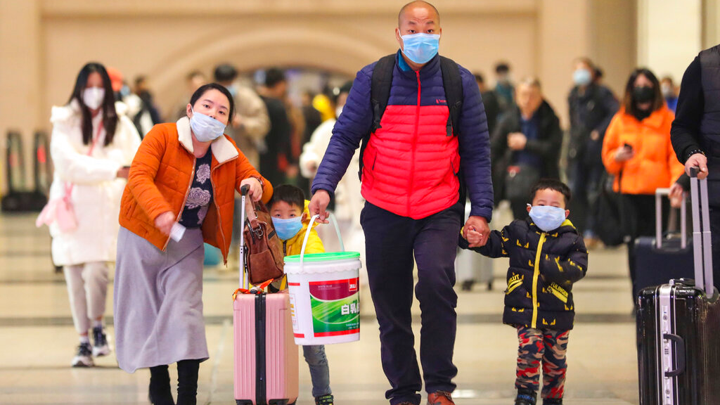 In this photo taken Tuesday, January 21, 2020, travellers wearing face masks walk with their luggage at Hankou Railway Station in Wuhan in southern China's Hubei province. (Chinatopix via AP)