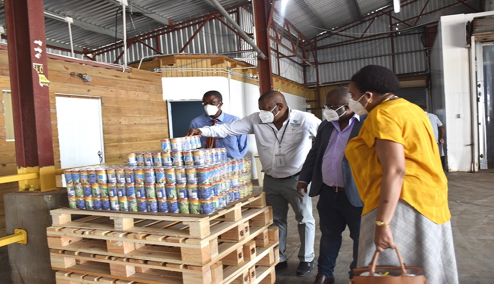 Regional Director of the Southern Regional Health Authority, Michael Bent (2nd left), Parish Manager of the Clarendon Health Services, Joseph Grant (left), CEO of Nation's Choice, Donald McDonald (2nd right) and Medical Officer of Health for Clarendon, Dr Kimberly Scarlett Campbell examine some of the items placed in food packages which will be distributed to more than 70 households and frontline healthcare workers in Cornpiece Settlement, Clarendon.