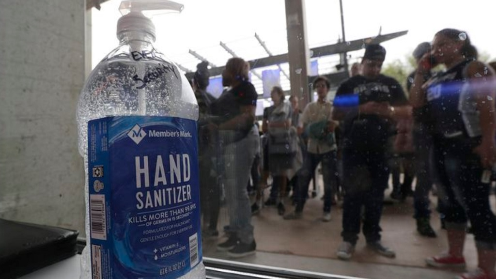 A large bottle of hand sanitizer sits next to a door as fans prepare to enter the arena for an NBA basketball game between the San Antonio Spurs and the Dallas Mavericks in San Antonio, Tuesday, March 10, 2020. (AP Photo/Eric Gay).