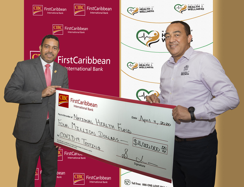 Nigel Holness (l), Managing Director of CIBC FirstCaribbean International Bank, presents the bank's donation of  $4 million to the Minister of Health and Wellness, Christopher Tufton, to support the Ministry's scaling up of testing for COVID-19.