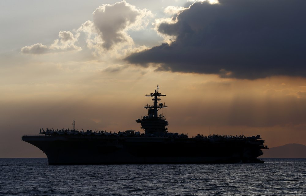 FILE - In this April 13, 2018, file photo the USS Theodore Roosevelt aircraft carrier is anchored off Manila Bay west of Manila, Philippines. The captain of the US Navy aircraft carrier facing a growing outbreak of the coronavirus is asking for permission to isolate the bulk of his roughly 5,000 crew members on shore, which would take the warship out of duty in an effort to save lives. The ship is docked in Guam (AP Photo/Bullit Marquez, File)