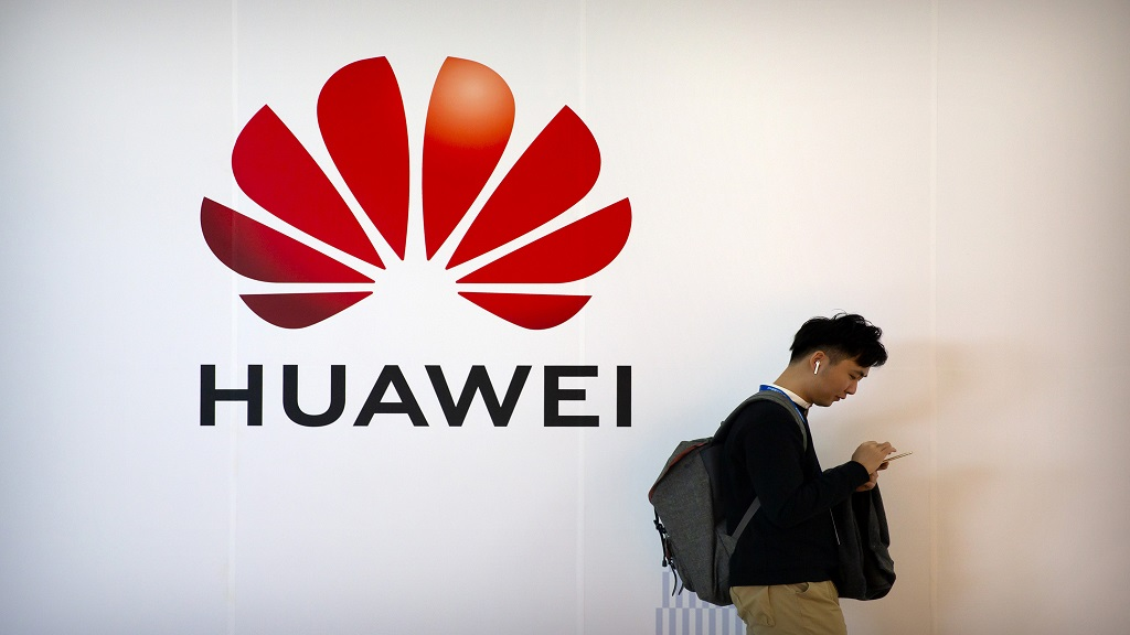 In this Thursday, Oct. 31, 2019, file photo, a man uses his smartphone as he stands near a billboard for Chinese technology firm Huawei at the PT Expo in Beijing. The Senate has passed a bill that provides $1 billion for small telecom providers to replace equipment in their networks that's made by China's Huawei and ZTE.