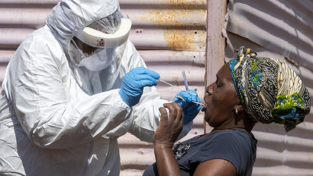 A woman opens her mouth for the heath worker to collect a sample for coronavirus testing during the screening and testing campaign aimed to combat the spread of COVID-19 at Lenasia South, south Johannesburg, South Africa, Tuesday, April 21, 2020. (AP Photo/Themba Hadebe)