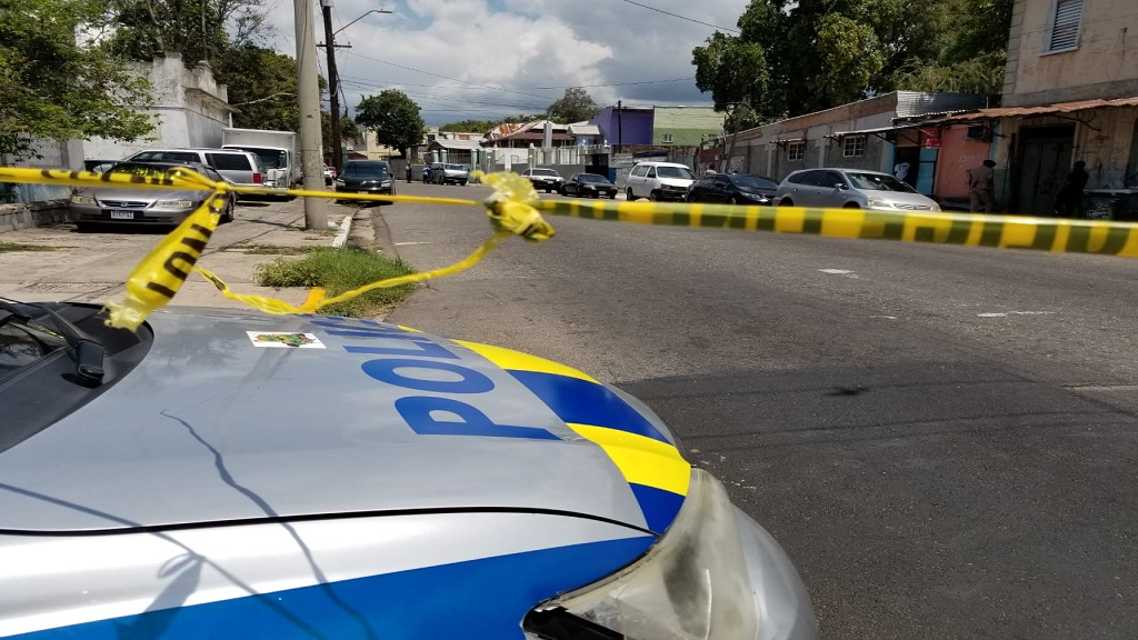 A police service vehicle is parked ahead of a cordoned section a crime scene along upper King Street in downtown Kingston on Wednesday.