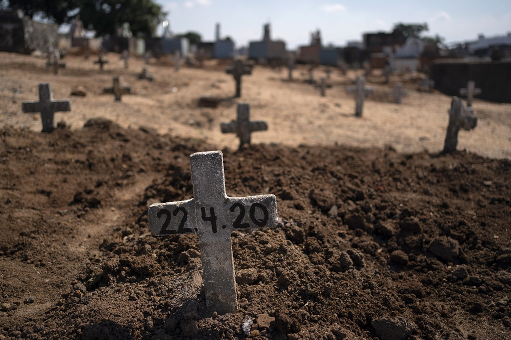 A cross with the date 22-4-20 marks the burial site of Edenir Rezende Bessa, who is suspected to have died of COVID-19, in Rio de Janeiro, Brazil, Wednesday, April 22, 2020. After visiting three primary care health units she was accepted in a hospital that treats new coronavirus cases, where she died on Tuesday. (AP Photo/Leo Correa)