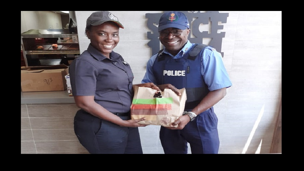 Lermena Edwards (left), Assistant Manager at Burger King Boulevard presents a package of sandwiches to Corporal Branford from Kingston West Police Station
