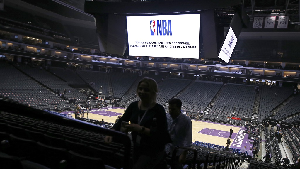 "In this March 11, 2020 photo, fans leave the Golden 1 Center in Sacramento, Calif., after the NBA basketball game between the New Orleans Pelicans and Sacramento Kings was postponed at the last minute over an ""abundance of caution"" after a player for the Jazz tested positive for the coronavirus. (AP Photo/Rich Pedroncelli, File)."