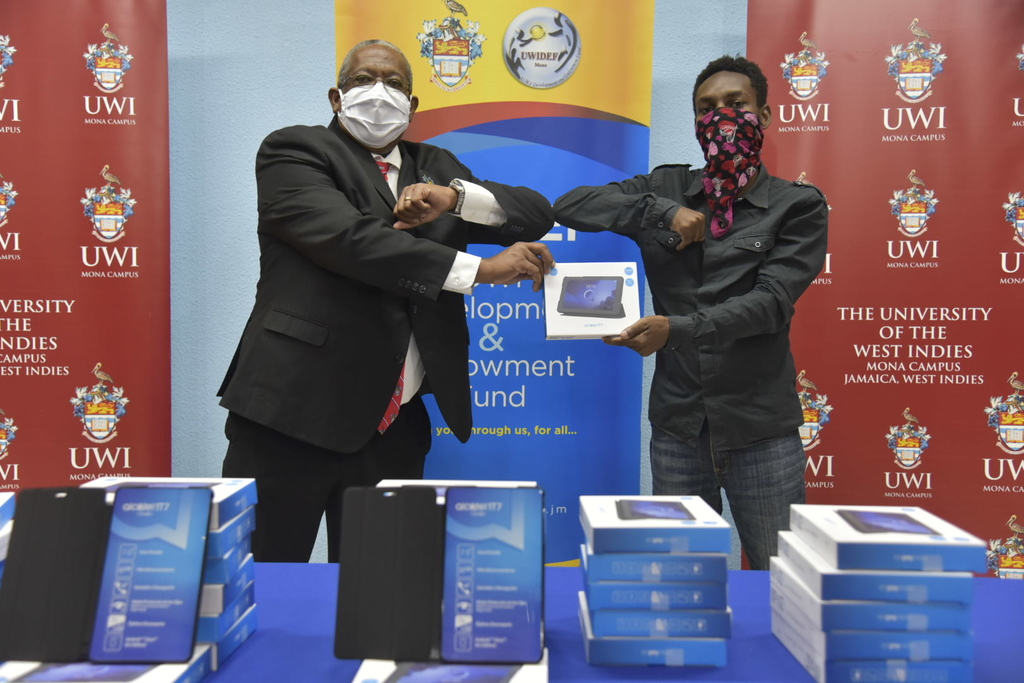 Professor Dale Webber, Principal of The UWI Mona elbow bumps final year student, Rodanne Corney who is one of the beneficiaries set to receive a device donated though a cross-sector partnership to support students in need, access online learning platforms.