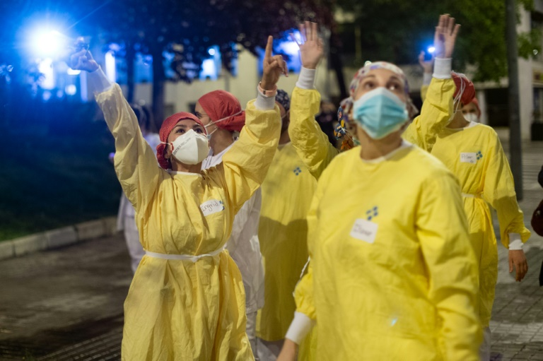 Des personnels soignants saluent les personnes qui les applaudissent devant l'Hôpital de Barcelone, le 13 avril 2020 en Espagne