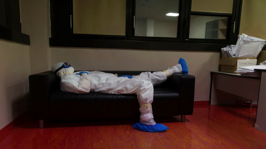 Doctor Giovanni Passeri relaxes in the doctor's lounge after completing a routine round of medical examinations during a night shift in his ward in the COVID-19 section of the Maggiore Hospital in Parma, northern Italy, Wednesday, April 8, 2020. (AP Photo/Domenico Stinellis)