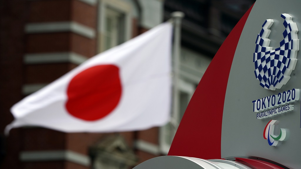 A Japanese flag is seen near Tokyo 2020 Paralympic logo at Tokyo Station in Tokyo Tuesday, April 21, 2020. An open conflict broke out Tuesday between Tokyo Olympic organisers and the IOC over how much to divulge about who will pay for the unprecedented year-long postponement. (AP Photo/Eugene Hoshiko)