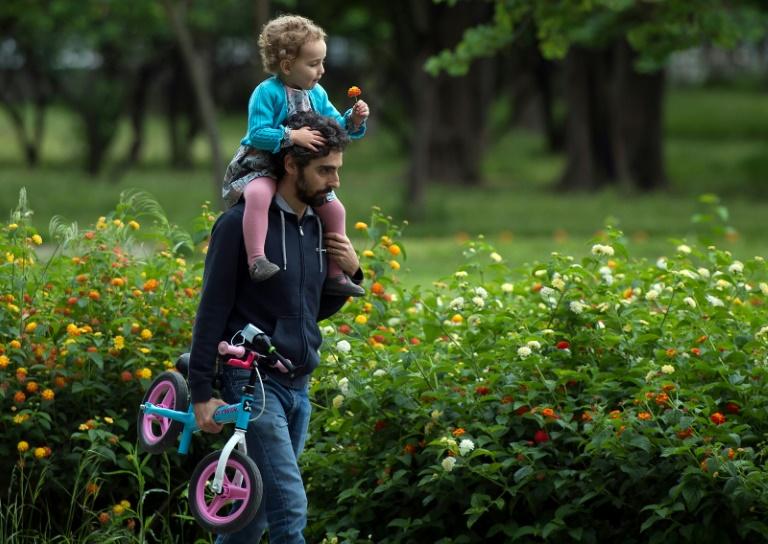 Un homme porte sa petite fille sur les épaules dans un parc à Séville, en Espagne, le 26 avril 2020