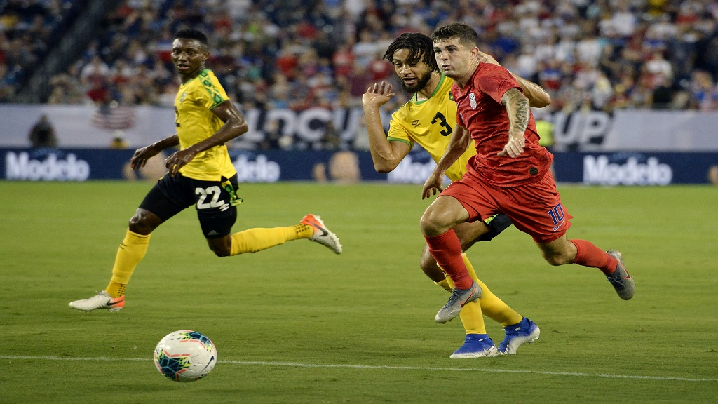 United States midfielder Christian Pulisic (10) moves the ball past Jamaica defender Michael Hector (3) during their  Concacaf Gold Cup semifinal football match on Wednesday, July 3, 2019, in Nashville, Tenn. The United States won 3-1.