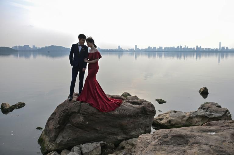 Un couple pose pour une photo de mariage, près d'un lac à Wuhan, dans la province du Hubei, en Chine, le 19 avril 2020