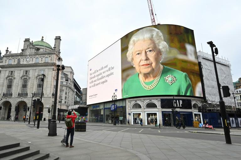 Photo géante de la reine Elisabeth II d'Angleterre, prise lors de son allocution à la nation dédiée à l'épidémie du coronavirus, sur une façade de Picadilly Square, à Londres, le 18 avril 2020 afp.com - Glyn KIRK