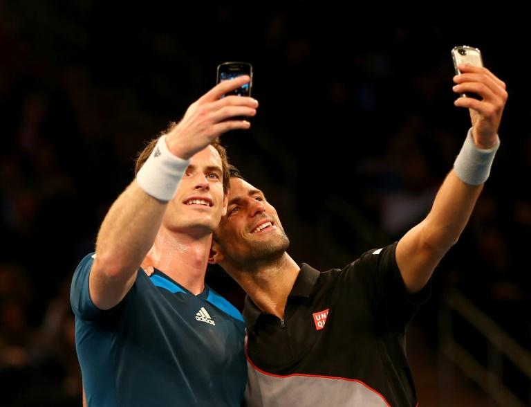 Le Britannique Andy Murray et le Serbe Novak Djokovic prennent des selfies avec leurs téléphones portables lors d'une exhibition à New York le 3 mars 2014