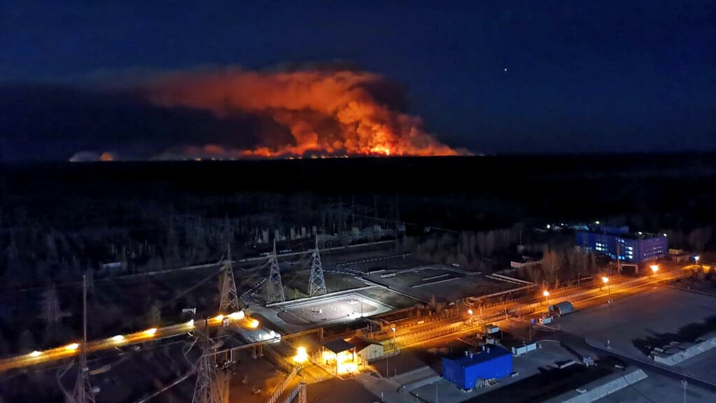 In this photo taken from the roof of Ukraine's Chernobyl nuclear power plant late Friday April 10, 2020, a forest fire is seen burning near the plant inside the exclusion zone. (Ukrainian Police Press Office via AP)