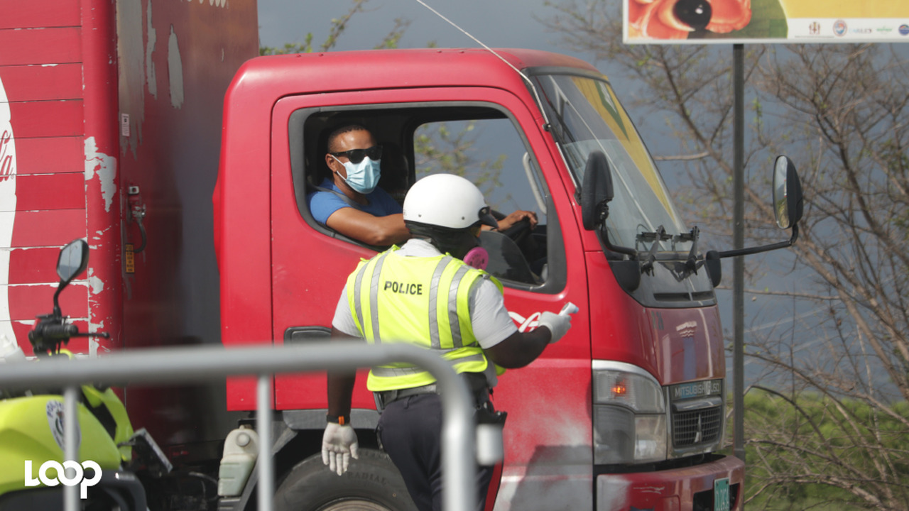 A police officer checks a truck driver's documents at a checkpoint in St Catherine, which is under lockdown. (Photo: Shawn Barnes)