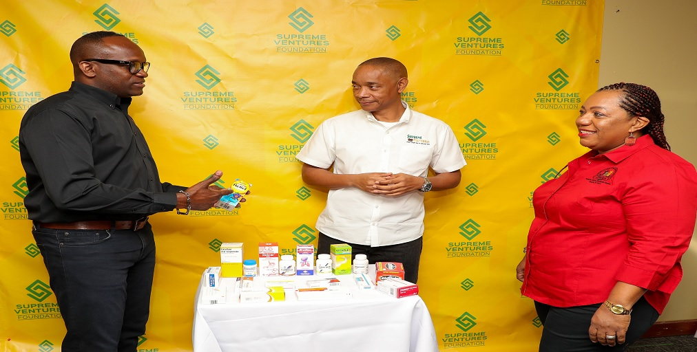 National Health Fund Pharmacy Director, Ainsley Jones (left) explains the importance of paediatric vitamins in boosting the immune system to Supreme Ventures Group CEO, Dennis Chung and CEO of the Child Protection and Family Services Agency (CPFSA), Rosalee Gage-Gray.