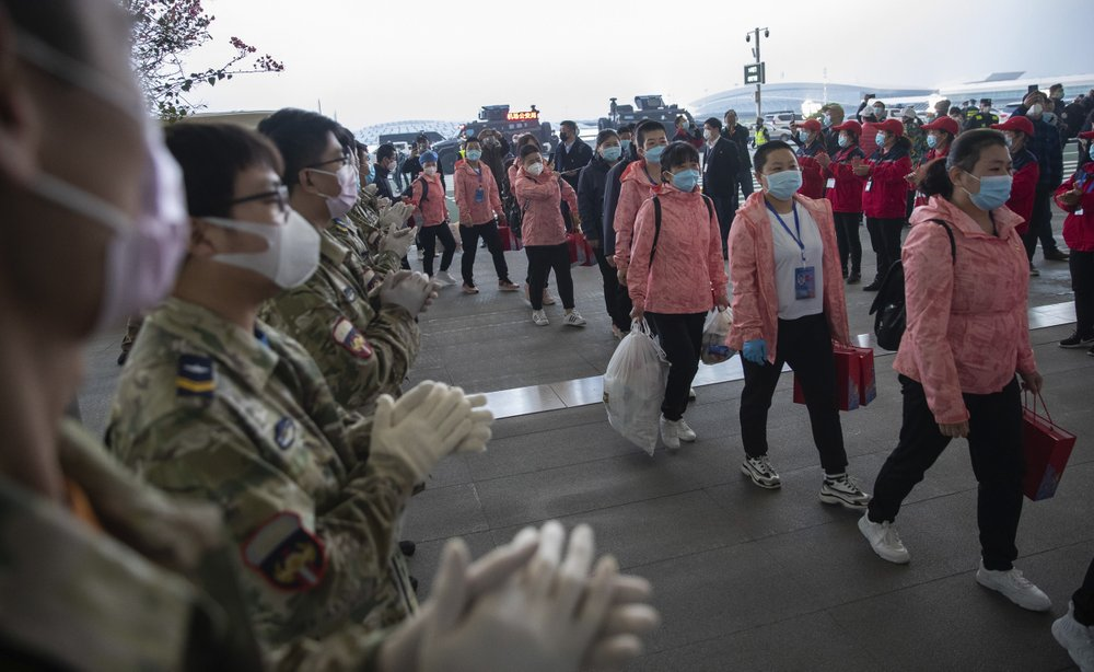 In this March 18, 2020 photo released by China's Xinhua News Agency, people applaud as departing medical workers enter Wuhan Tianhe International Airport in Wuhan in central China's Hubei Province. (Ke Hao/Xinhua via AP)