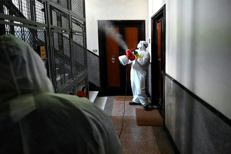 Des employés désinfectent la cage d'escalier d'un immeuble, le 31 mars 2020 à Rome, pour lutter contre la pandémie de coronavirus afp.com - Alberto PIZZOLI