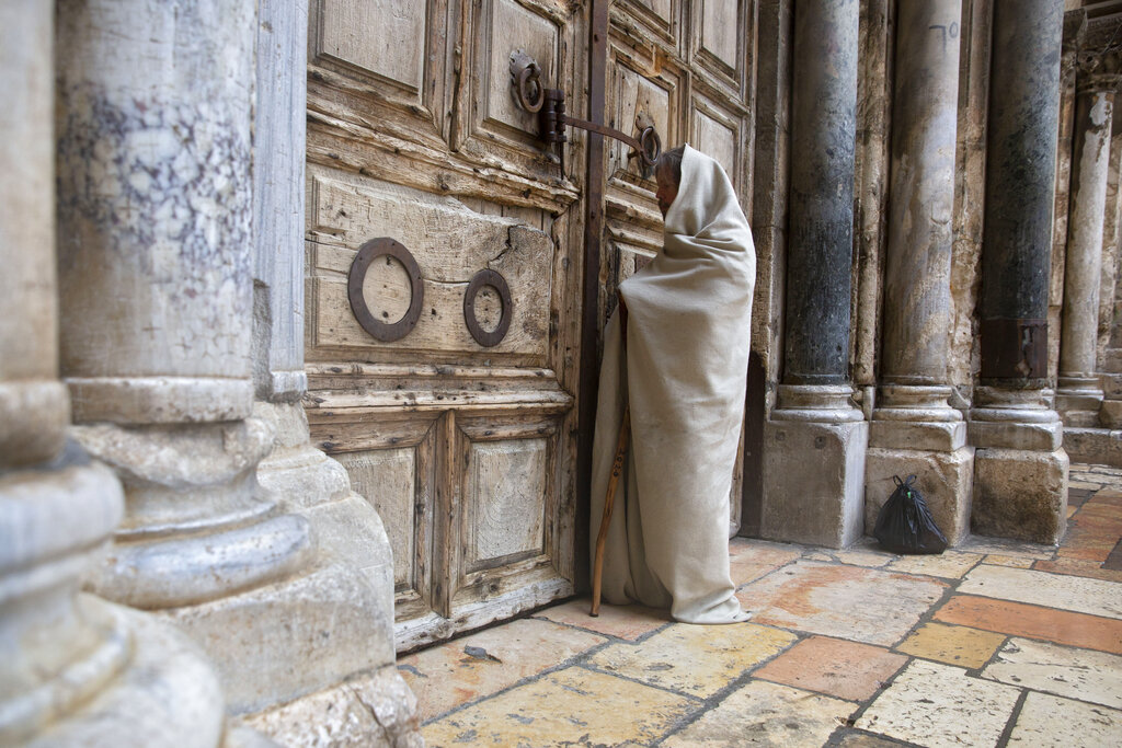 A Christian worshiper stands at the closed door of the Church of the Holy Sepulchre, believed by many Christians to be the site of the crucifixion and burial of Jesus Christ, in Jerusalem, Friday, April 10, 2020.