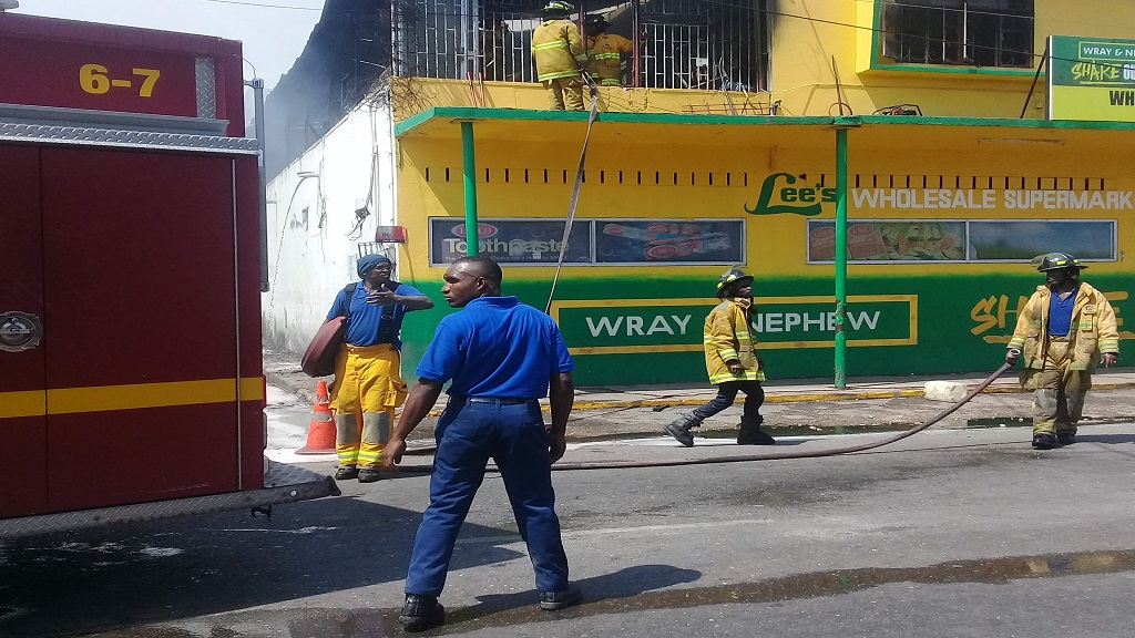 Firefighters performing cooling down operations at the Lee's Wholesale Supermarket Meat and Liquor store in Old Harbour, St Catherine on Monday.