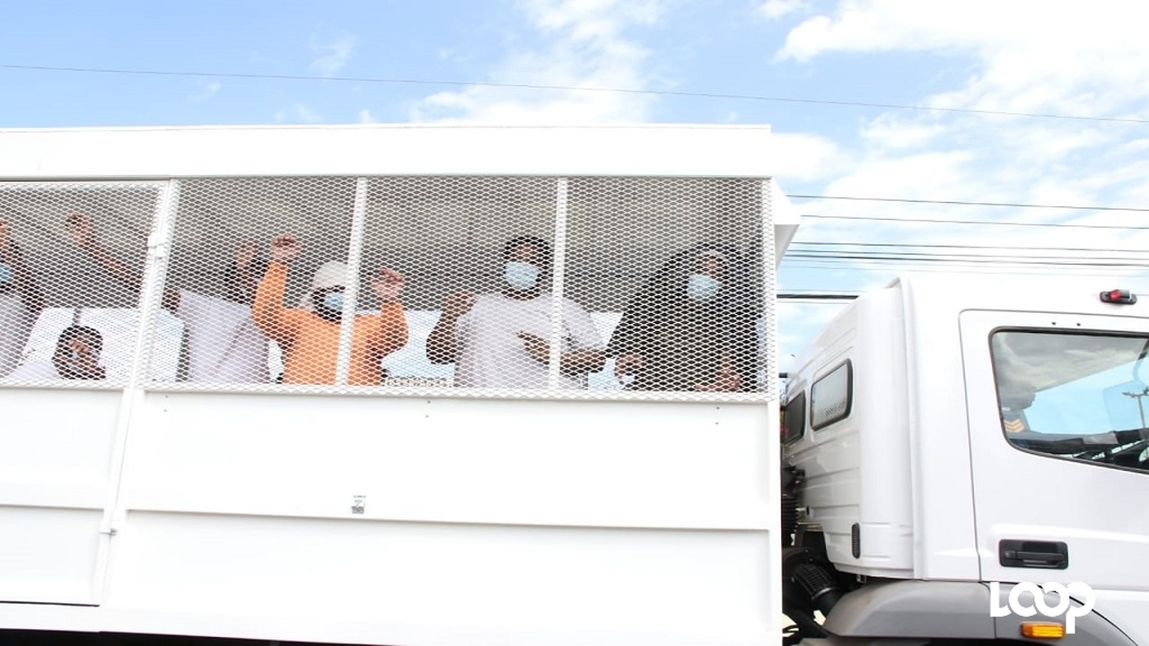 Returned residents inside the back of a police truck as it arrives at the Knutsford Court Hotel in St Andrew on Tuesday.