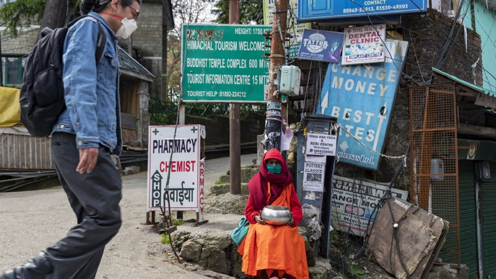 A Buddhist monk wears a mask to protect himself from coronavirus infection as he sits in a town square seeking alms in Dharmsala, India, Monday, April 20, 2020. India recorded its biggest single-day spike in coronavirus cases on Monday as the government eased one of the world's strictest lockdowns to allow some manufacturing and agricultural activity to resume. (AP Photo/Ashwini Bhatia)