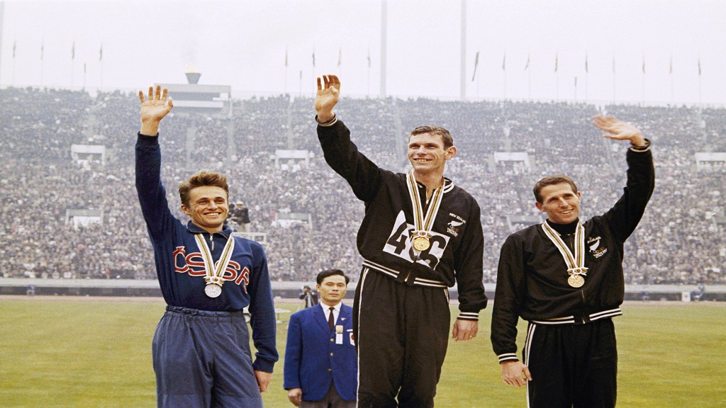 In this Oct. 21, 1964 file photo, gold medalist Peter Snell, centre, of New Zealand, silver medalist Josef Odlozil, left, of Czechoslovakia, and bronze medalist John Davies of New Zealand, right, stand on podium with their awards in the Olympic 1,500m at the Tokyo Summer Games. The one-year postponement of the Tokyo Olympics has inspired organisers of a track meet in the Czech Republic to go ahead with their event in June.