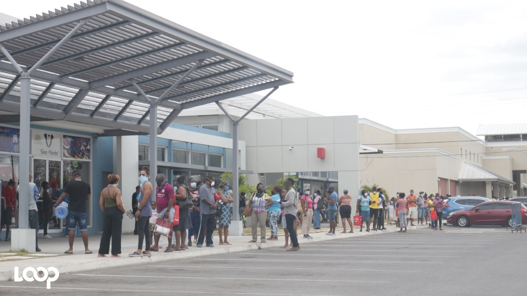 Shoppers in a long and winding line to get into a major supermarket in Portmore, St Catherine last Wednesday.