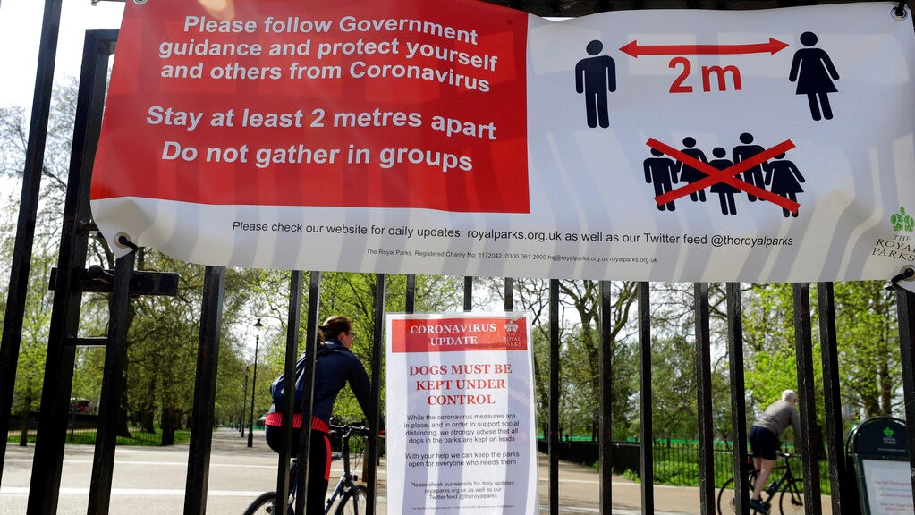 A sign in Hyde Park in London advises social distancing, as the country is in lockdown to help curb the spread of the coronavirus, Monday, April 13, 2020. (AP Photo/Kirsty Wigglesworth)