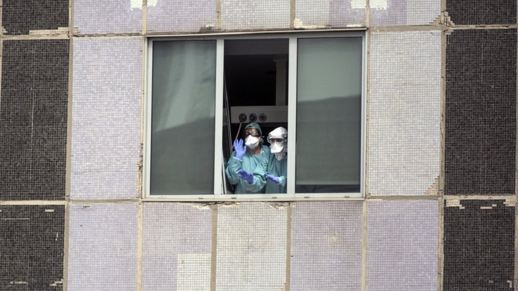 Health workers look hospital windows amid the coronavirus outbreak in Spain.  (AP Hoto)