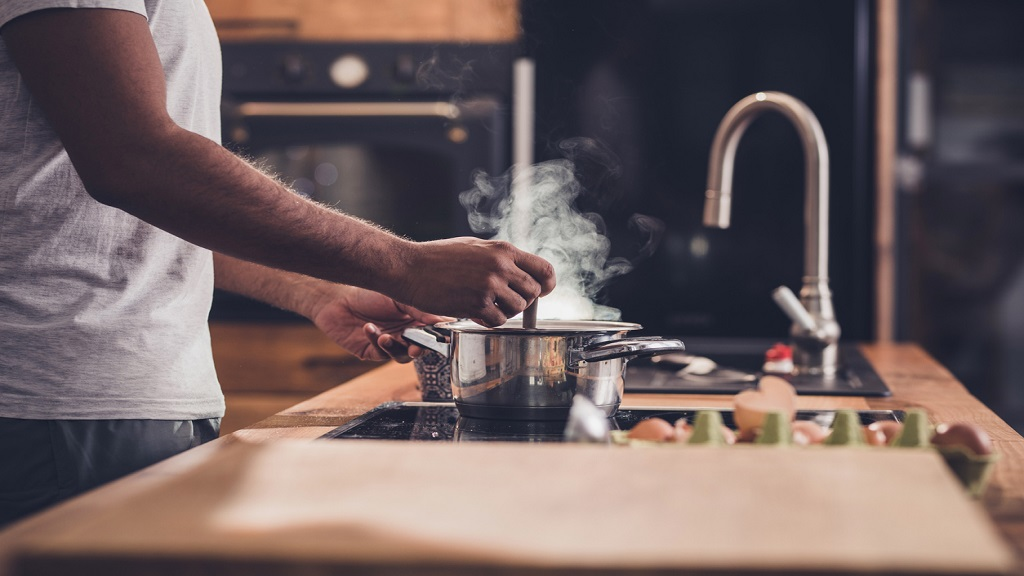 iStock photo of a man making lunch in the kitchen and stirring soup.