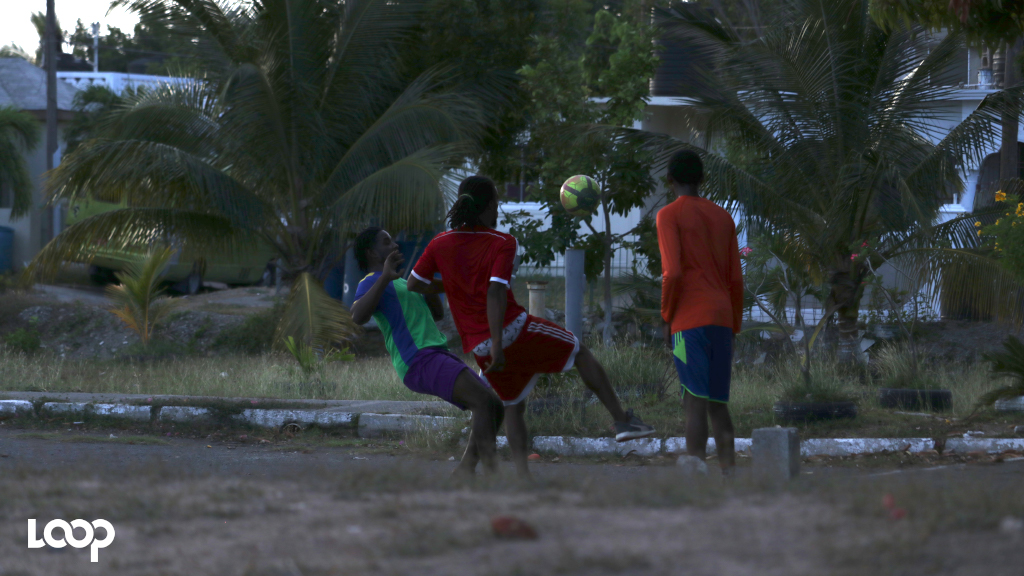 A group of boys playing football at a field in Portmore, St Catherine this week amid government's shutdown on public gatherings due to COVID-19. (Photo: Shawn Barnes)