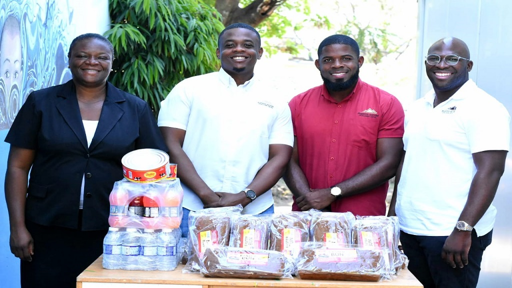 From left, Nadine Waugh, Director of Jamaica National Children's Home; Morris McKenzie, General Manager, Puerto Anton Developers Limited; Mikael Watson, Regional Manager of the company; and Rashanne Henry, Director, participate in the donation of 100 Easter buns, tins of cheese, cases of water, and cases of juices to the Jamaica National Children's Home in Papine, St Andrew on Thursday.
