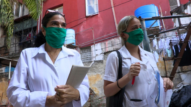 Liz Caballero Gonzalez (g), médecin, et l'étudiante en médecine Susana Diaz font du porte à porte dans le quartier du Vedado, le 31 mars 2020 à La Havane, pendant l'épidémie de coronavirus à Cuba