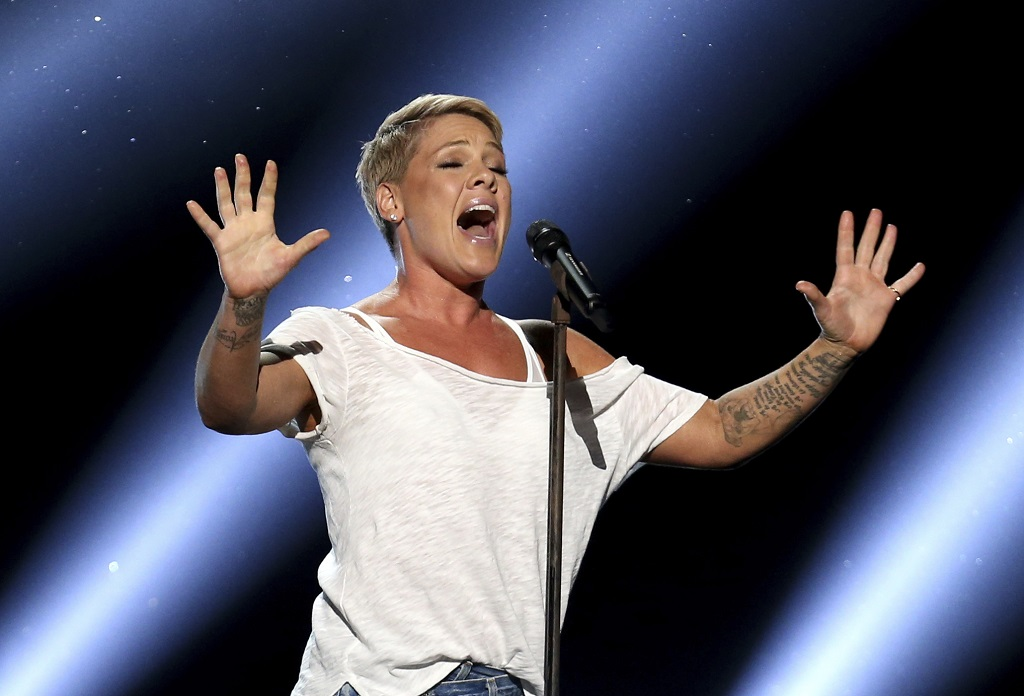 "FILE - In this January 28, 2018, file photo, Pink performs ""Wild Hearts Can't Be Broken"" at the 60th annual Grammy Awards at Madison Square Garden in New York. Pink says she had COVID-19 and is donating $500,000 each to two emergency funds. In a pair of tweets posted April 3, 2020, the singer says she tested positive after she and her three-year-old son started displaying symptoms two weeks ago. (Photo by Matt Sayles/Invision/AP, File)"